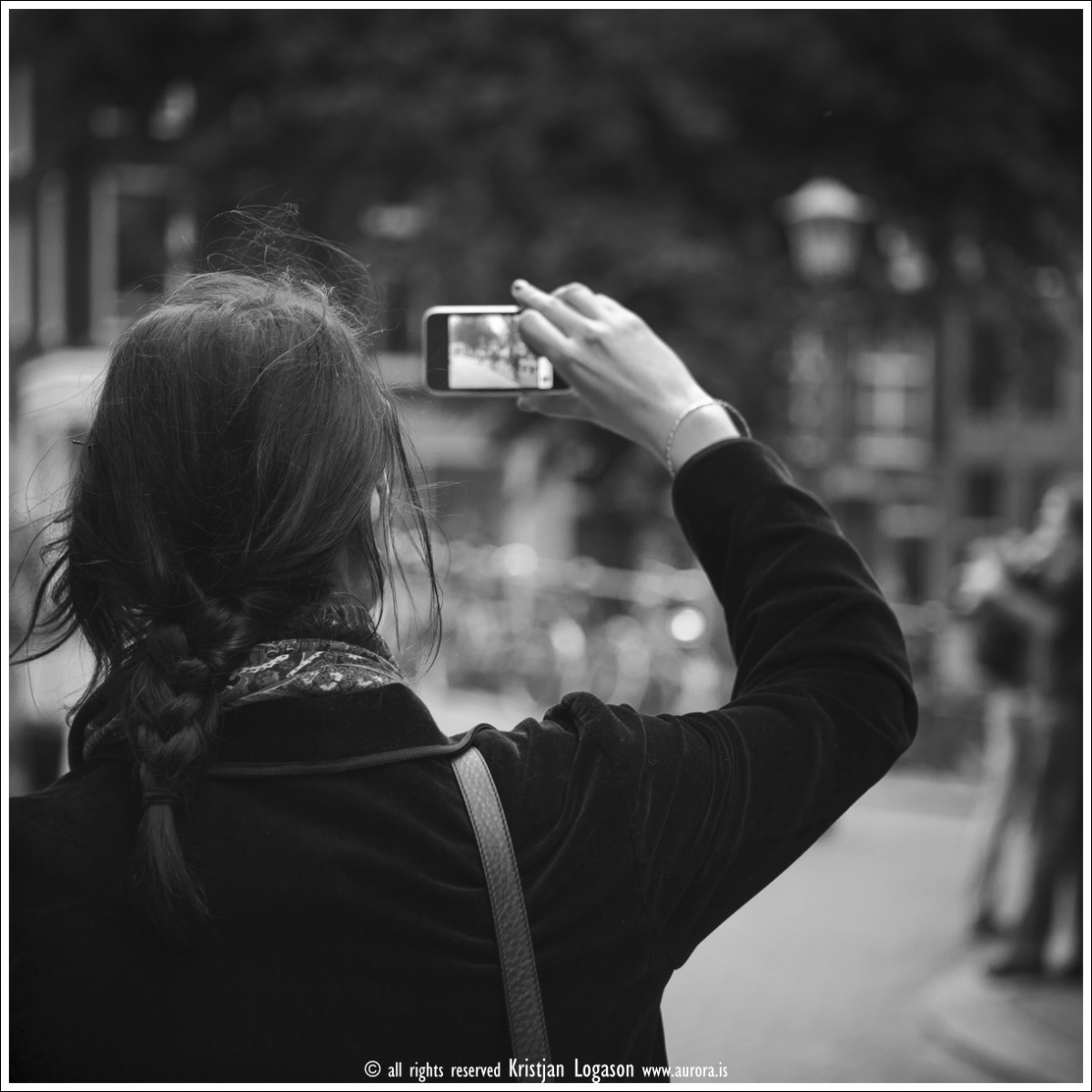 Woman tourist with braids in here hair standing on a street in central Amsterdam taking pictures with here iPhone