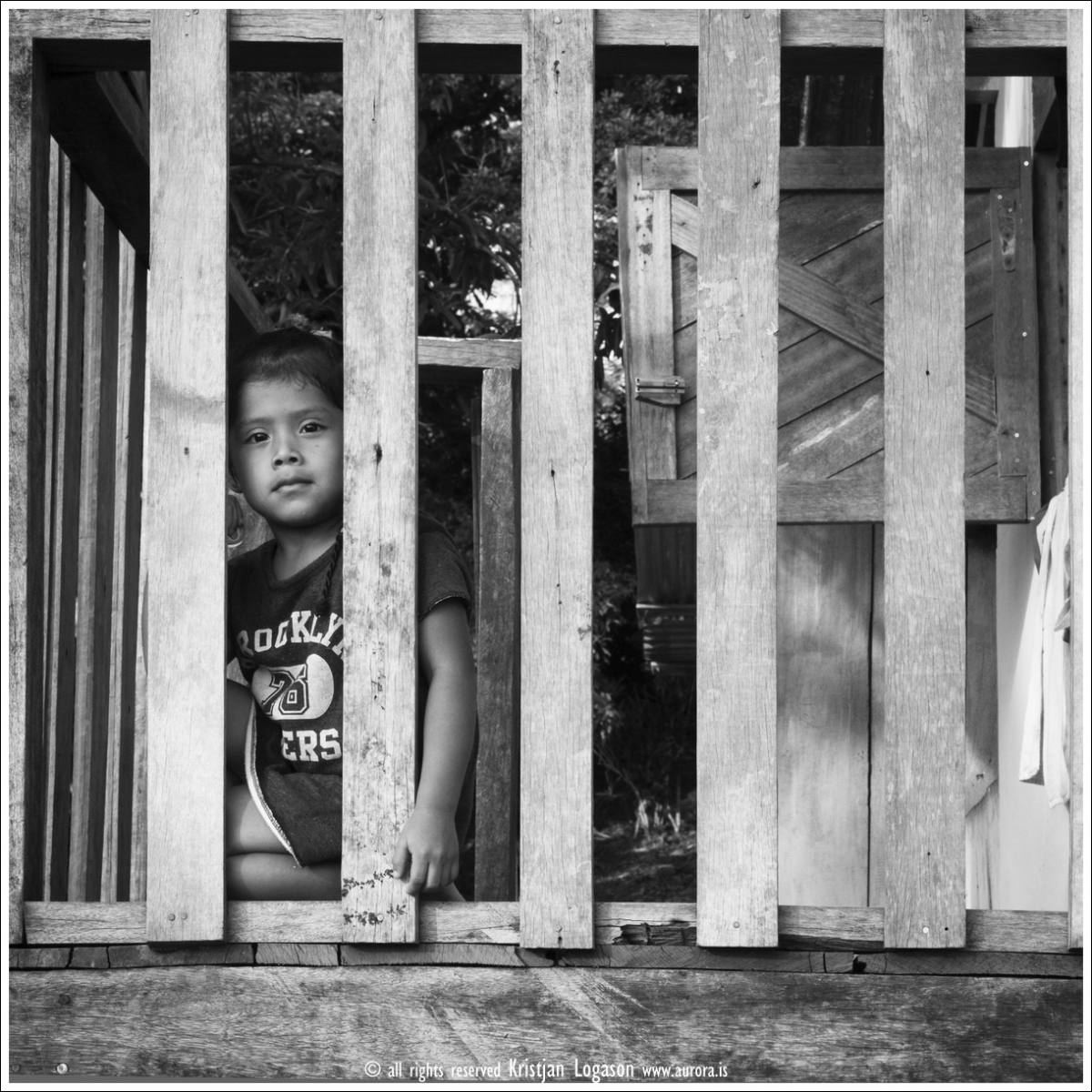Young boy in Bocas del Toro looking through the front porch balcony handrail