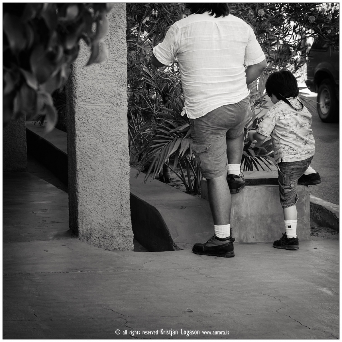 Father and son eating Ice cream stand in same position, in a street of Todos Santos Baja california, Mexico