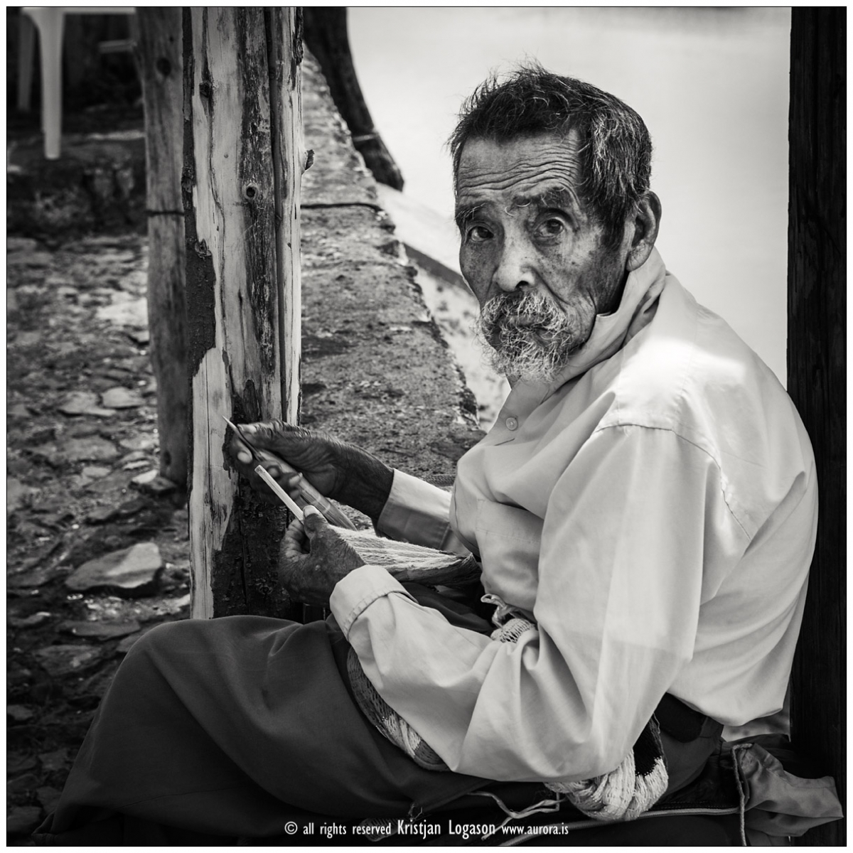 Old man  in the street of Janitzio knitting