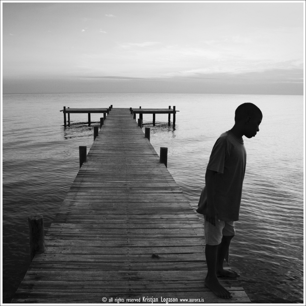 Young boy standing on the jetty in central Hopkins in,Belize, looking for fish and manatee