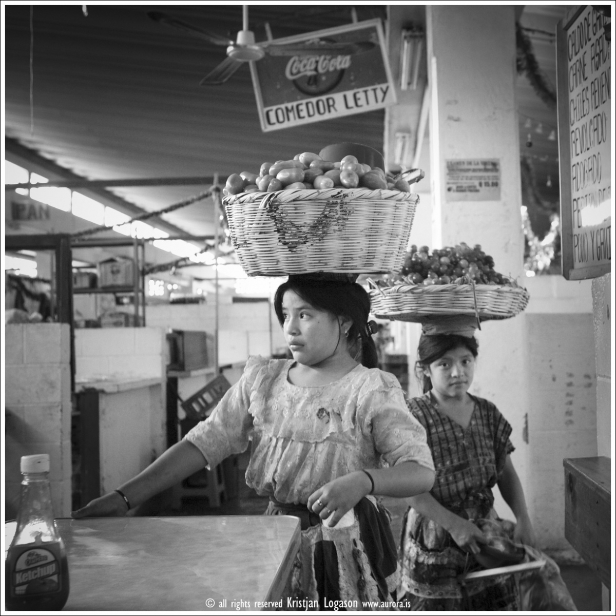 Young girls selling vegetables and fruits at the market in Antigua, Guatemala