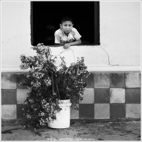 Young boy looking out a window of his pink home in Ataco, El Salvador