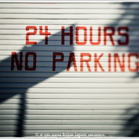 24 hours no parking painted on a garage door